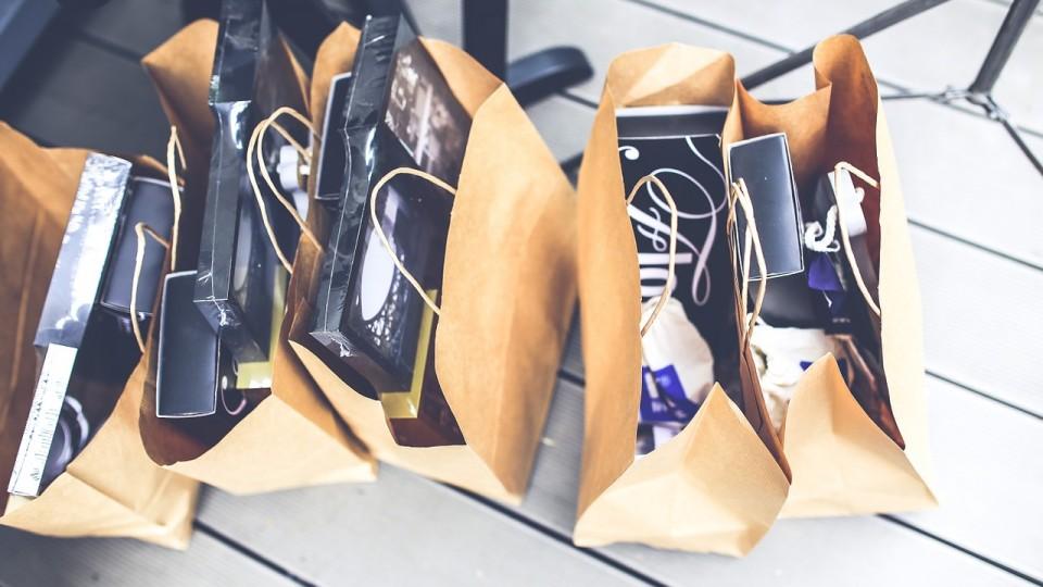 Papirsposer fra Vinsmagning og Premium Outlet Shopping TourPremium Outlet Shopping Tour® står i række på et hvidt trægulv